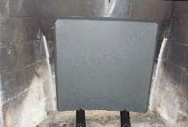 A heat shield in front of a masonry firebox repair