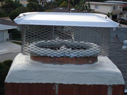 A chimney with a top sealing damper and chimney cap